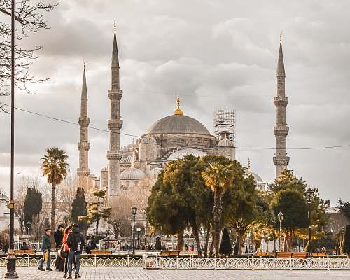 building people walking near trees and Blue Mosque dome