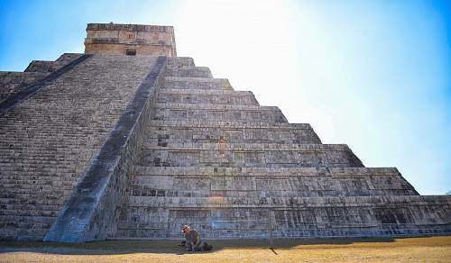 building person sitting on grass field in front on gray concrete pyramid mexico