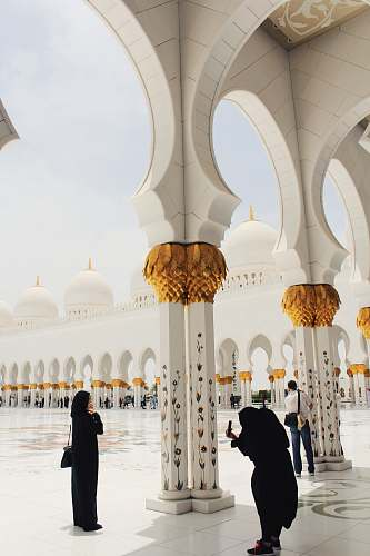 building person taking picture of woman wearing abaya and hijab during daytime dome