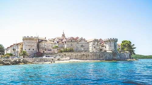 castle photo of gray concrete establishment near the body of water urban