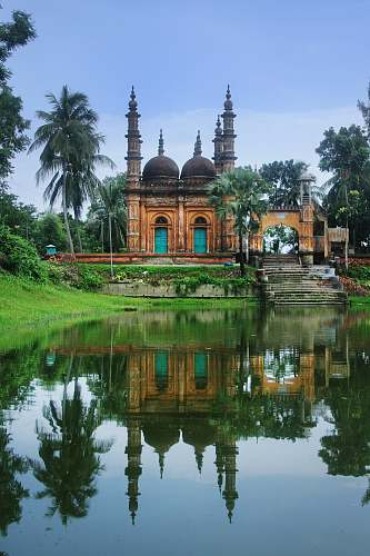 building photography of brown mosque beside body of water during daytime dome