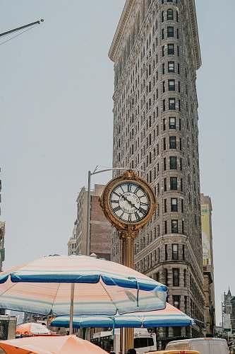 building round analog clock near Flatiron building at New York during daytime tower