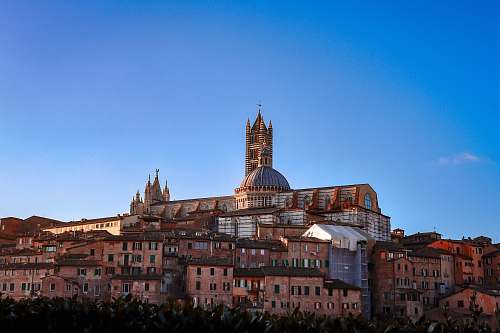 building Siena Cathedral in Italy under blue and white sky spire