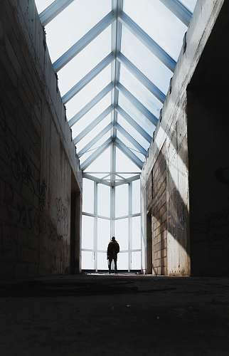 building silhouette of man standing inside abandoned building window