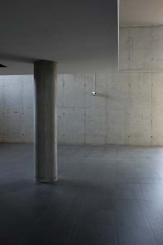 building The inside of a building made of concrete walls with a platform supported by pillars. grey