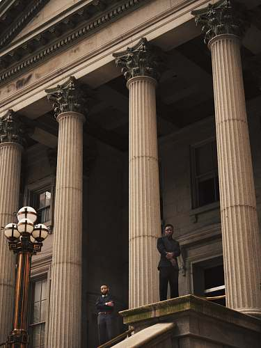 building two men standing on Corinthian column building pillar