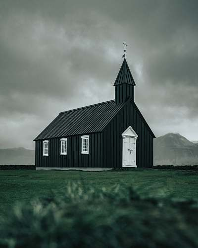 building white and black wooden church on green field viewing mountain during daytime tower