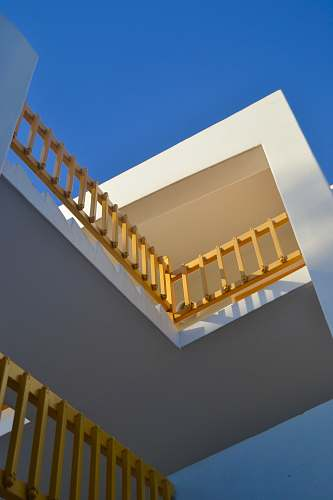 building white concrete building with yellow wooden railings window
