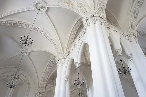 building white concrete pillared building with chandeliers arched