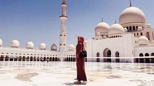 building woman in red dress walking near mosque dome
