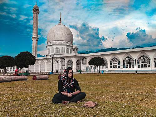 building woman wearing gray hijab sitting in front of dome building dome