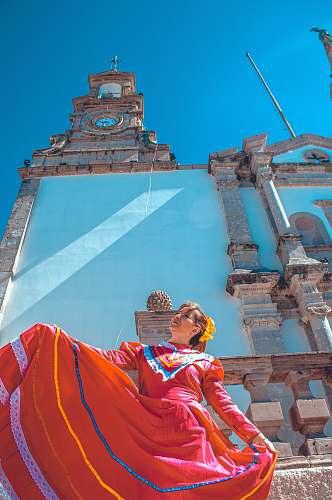 building woman wearing orange dress near church tower