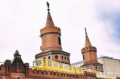 spire yellow train beside castle building