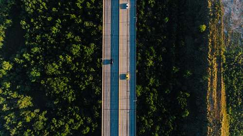 architecture aerial photography of vehicle traveling on bridge during daytime tower