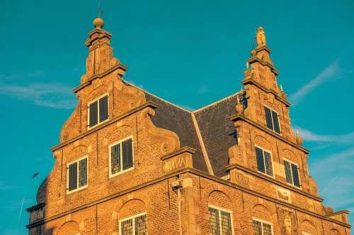 architecture brown brick building under blue sky spire