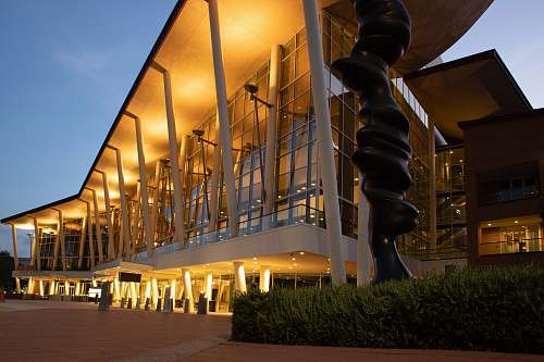 architecture lighted white and brown concrete buildings with glass wall convention center