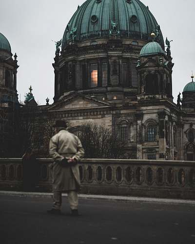 dome man walking on bridge near brown concrete dome building architecture