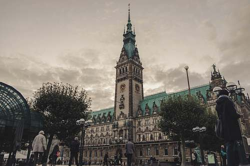 architecture people walking near Hamburg City Hall in Germany under gray skies during daytime tower