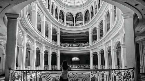 architecture woman standing beside balustrade black-and-white