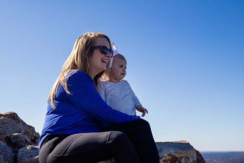 accessory woman in blue sweater and black pants sitting on rock during daytime sunglasses
