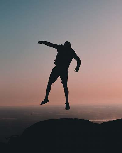 gliding silhouette of man jumping on cliff at golden hour leisure activities