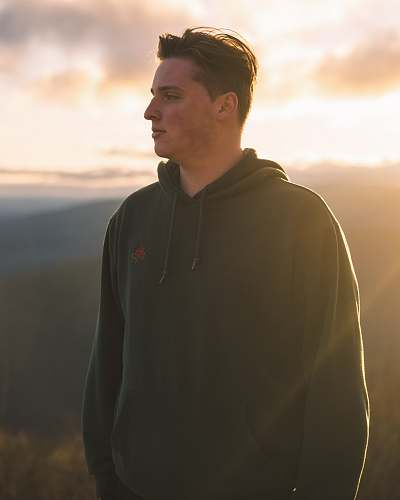 clothing man in black hoodie standing on hill during daytime human