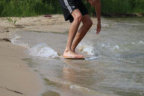 clothing person in black shorts running on water during daytime shorts