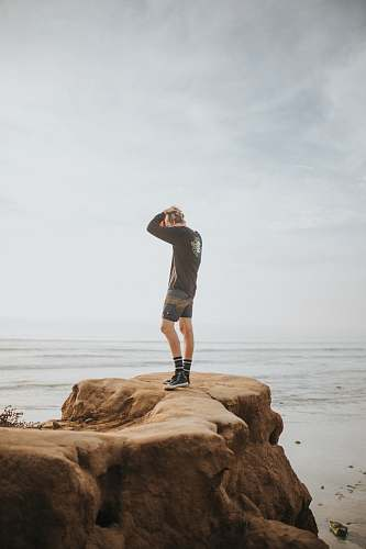 clothing person standing on rock formation during daytime shorts
