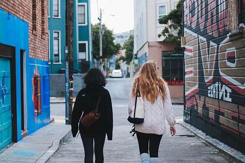 clothing two women in sweaters walking on street human