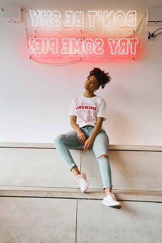 clothing woman in white crew neck t-shirt and blue denim jeans sitting on white concrete wall footwear
