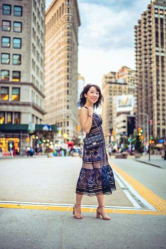 clothing woman standing in center of street near buildings skirt