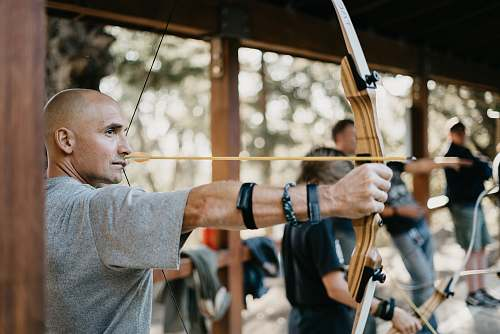 bow man using a brown bow sport