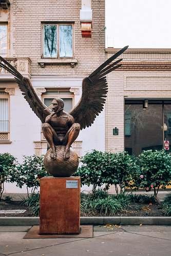 sculpture brown concrete statue of man holding book statue