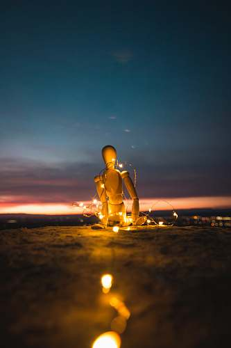 buddha marionette doll on stand with LED string lights worship