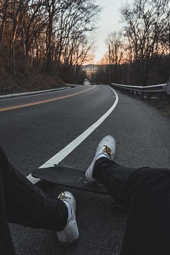 tarmac person sitting on road with longboard cincinnati