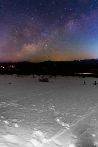 night snow field near mountain under starry night universe