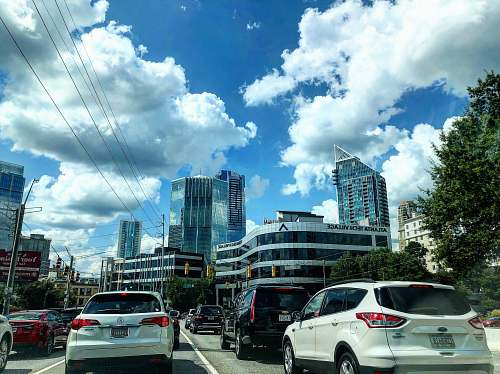 car different vehicles on road viewing city with high-rise buildings under white and blue skies transportation