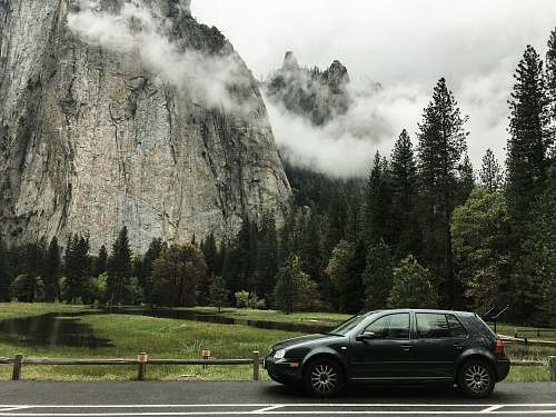 transportation gray 5-door hatchback on the road near trees and mountain car