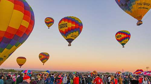 sphere people gathering below multicolored hot air balloons ball