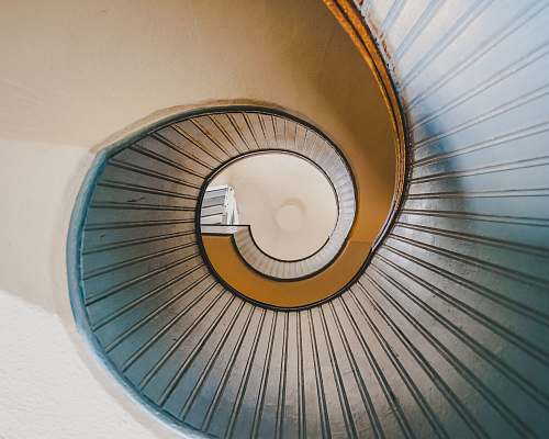 handrail low angle photography of spiral ladder staircase