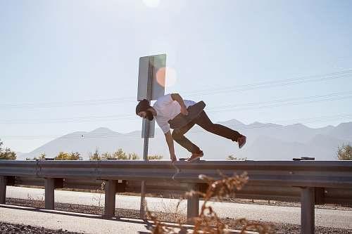 jump man crossing on road fence while holding black skateboard utah lake