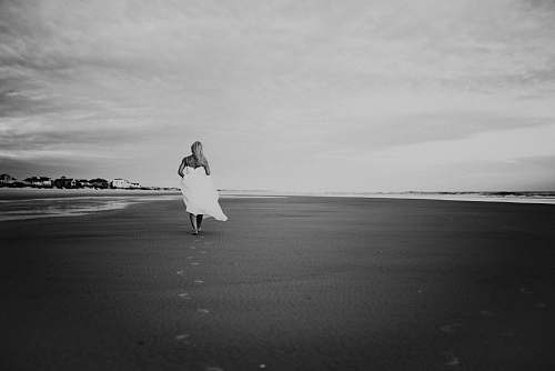 black-and-white grayscale photo of woman walking on seashore grey