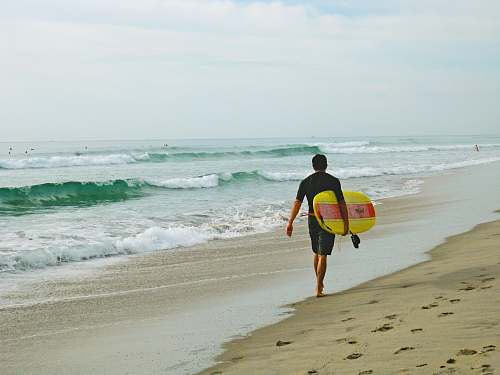 coast man carrying surfboard while walking on shore ocean