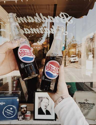 coke person holding Pepsi Cola soda bottles drink