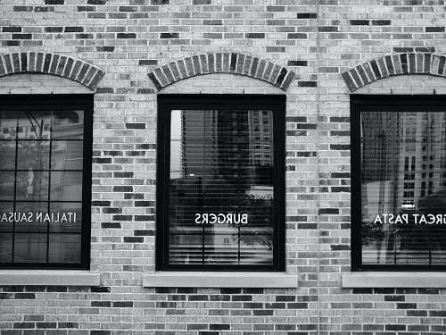 brick grayscale photography of building with glass windows chicago