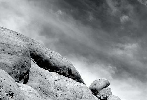 rock grayscale photography of mountain cloud