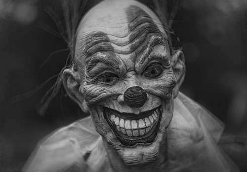 human grayscale photography of person wearing clown mask grey