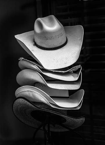 hat grayscale photography of piled cowboy hats clothing