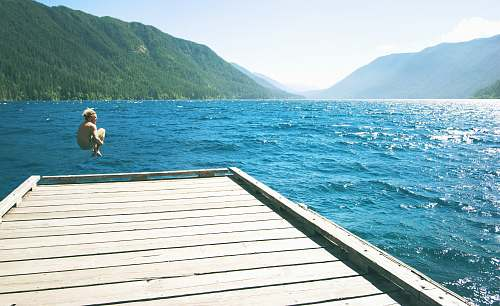 lake crescent topless person jumping towards water from white wooden dock dock