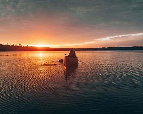 canoe person sailing canoe during sunset rowboat